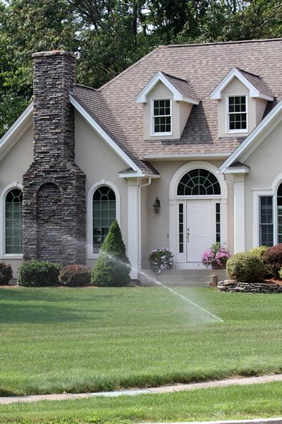 lawn sprinkler in yard of beautiful home